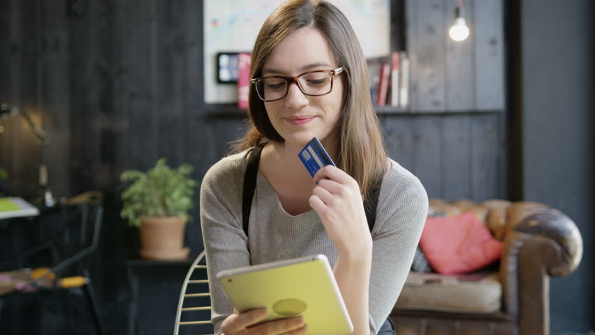 Young Woman Holding Her Credit Card About To Make An Online Shopping Purchase On An iPad Digital Ecommerce Making A Decision For Online Payment Concept Slow Motion Shot On Red Epic 8K