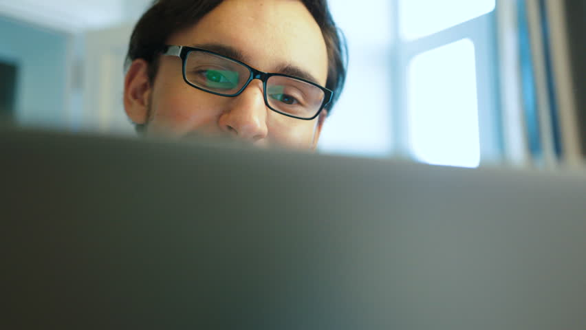 Portrait of young happy man in casual blue shirt with glasses watching funny video on the laptop in the living room while sitting on sofa. | Shutterstock HD Video #28459618
