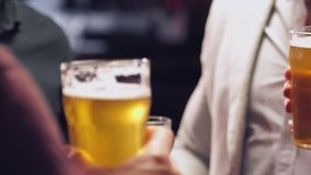 Cropped video of young men friends drinking beer and talking with each other in bar