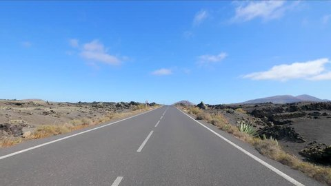 POV: Solitary road in the desert with blue sky on the island of Lanzarote, Canary Islands. Spain, Europe.