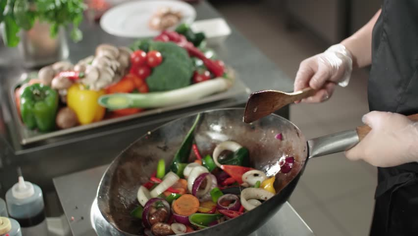Close-up cook actively roasting mixed colorful vegetables wok-tossing in the kitchen of an Asian restaurant, slow motion