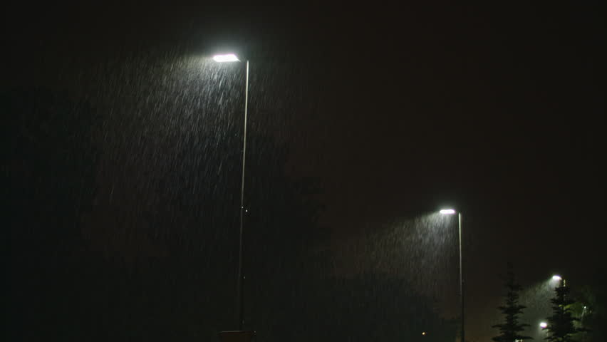 Rainy street at night. A row of lampposts illuminating raindrops. Long shot.