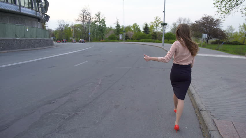 Young beautiful business lady walking on the road and trying to hitch a car #28492639