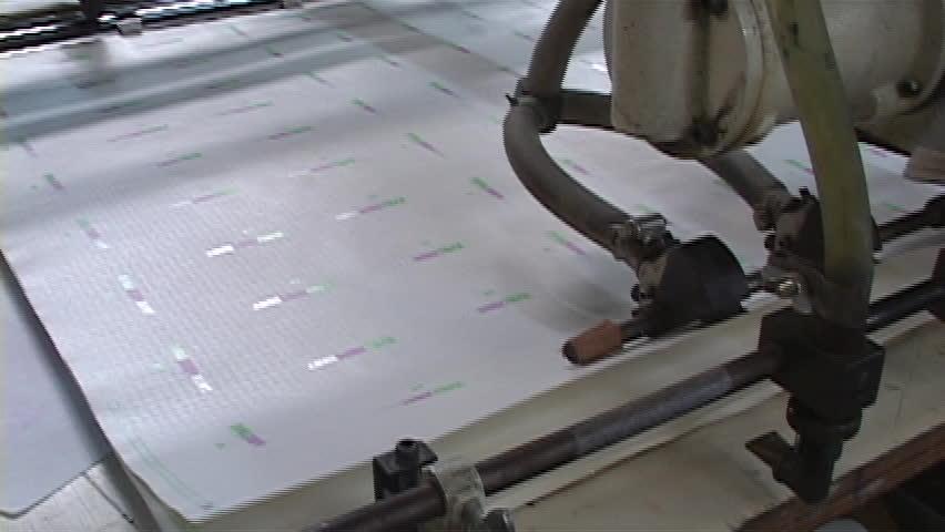 T-Shirt factory paper roll being sent through decal machine. | Shutterstock HD Video #28495