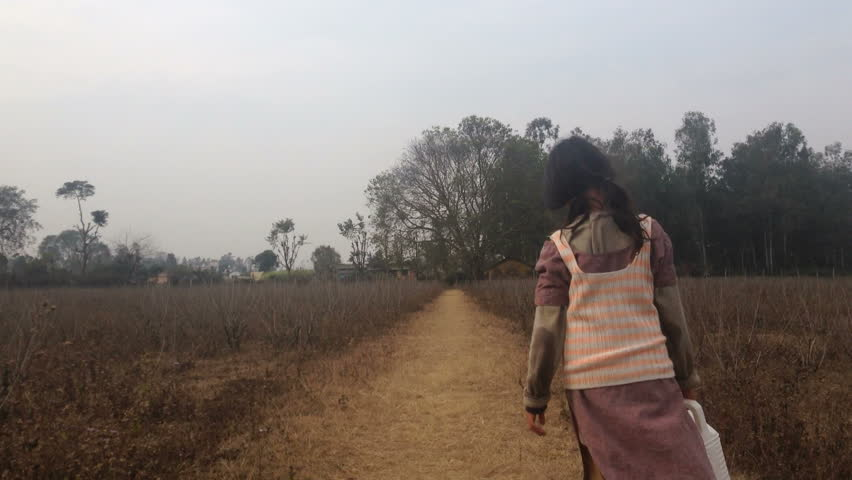 Poor little Indian village girl walking through the fields with a water container.