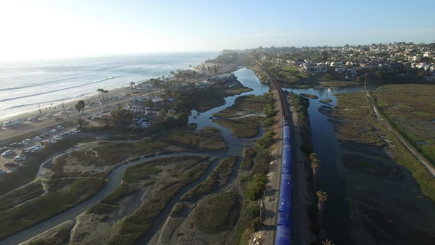High aerial over an Amtrak train traveling beside the Pacific ocean near San Diego. (San Diego, California 2010s)