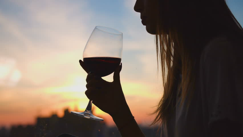 Young woman drinking red wine from a glass and watching on sunset through the window. Close up. Stay at home.