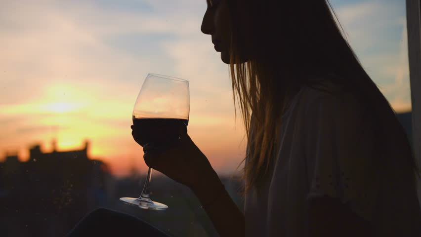Portrait of young woman drinking red wine from a glass and watching on sunset through the window. Close up. | Shutterstock HD Video #28519855