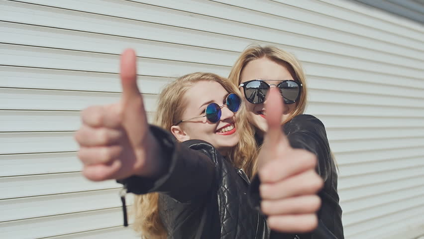 Two smiling stylish girls in leather jackets and sunglasses show a gesture of thumbs up. Background of white horizontal rolling shutters.