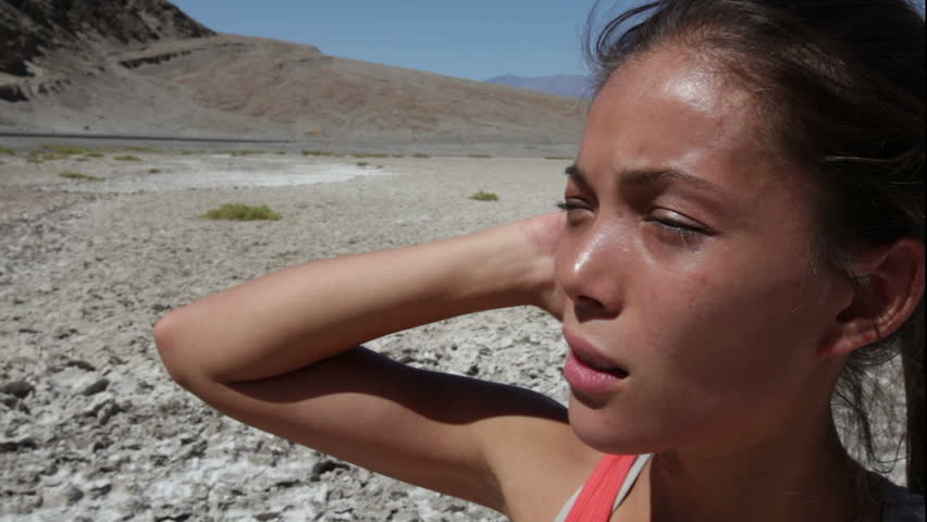 Thirst - dehydrated thirsty woman sweating in Death Valley desert, USA. Woman suffering from dehydration and exhaustion.