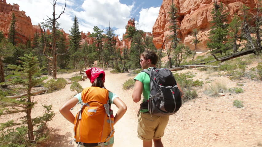 Hiking backpackers on hike in beautiful landscape in Bryce Canyon National park trekking smiling happy together. Multiracial couple, young Asian woman and Caucasian man in Utah, USA.