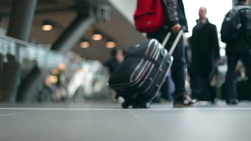 Passengers with luggage at a modern Station in 1080p HD with bokeh