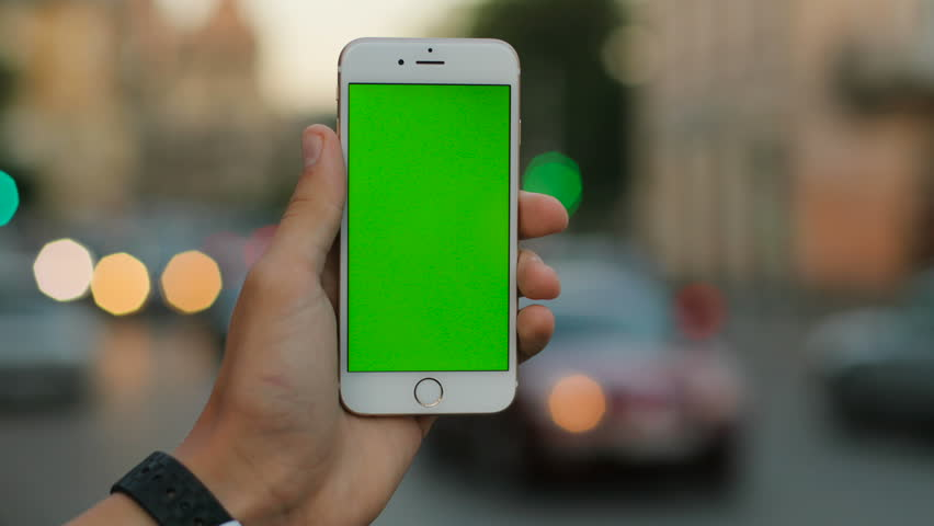 NEW YORK - January 17, 2016: Male hands holding white smartphone with green screen on the city street background in the evening. Close up. Chroma key | Shutterstock HD Video #28572019