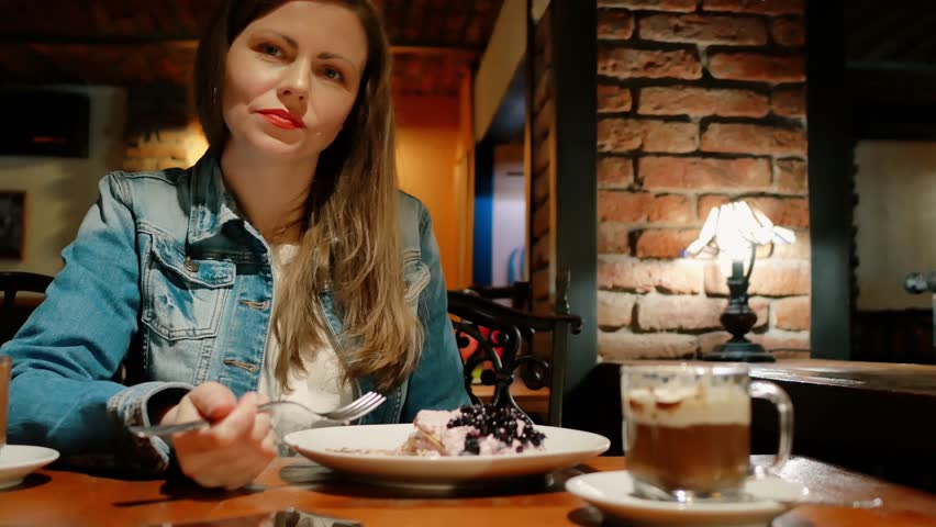 Pretty girl in a cotton jacket eats dessert with a hot chocolate in a cafe. Vintage interior. Brick wall.