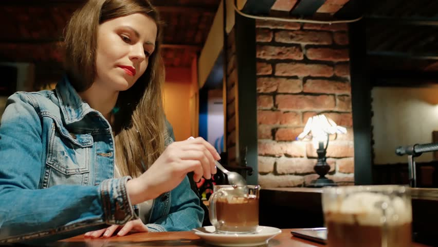 Pretty girl in a cotton jacket with a hot chocolate in a cafe. Vintage interior. Brick wall.