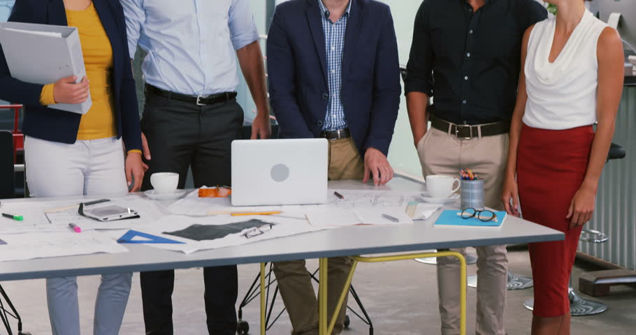 Cheerful business executives standing with blueprint in office | Shutterstock HD Video #28611415