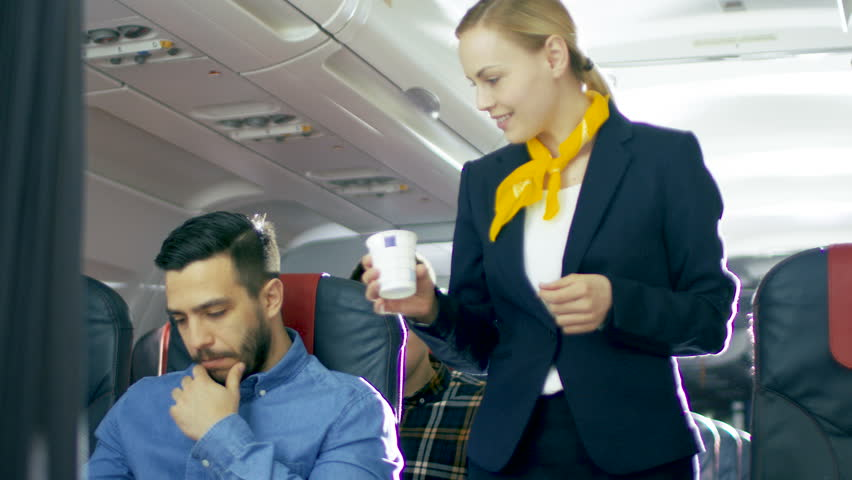 Airplane Stewardess/ Flight Attendant Brings Coffee for Handsome Hispanic Male Gentleman. They're Inflight. Business Class of a Commercial Aviation Interior is Visible.