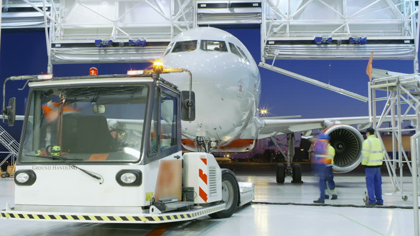 Time-Lapse of a Aircraft Maintenance Hangar Where New Airplane is Toed by a Pushback Tractor/ Tug onto Landing Strip. Crew of Mechanics, Engineers and Drivers Works Busily. Shot on RED EPIC-W 8 Camera
