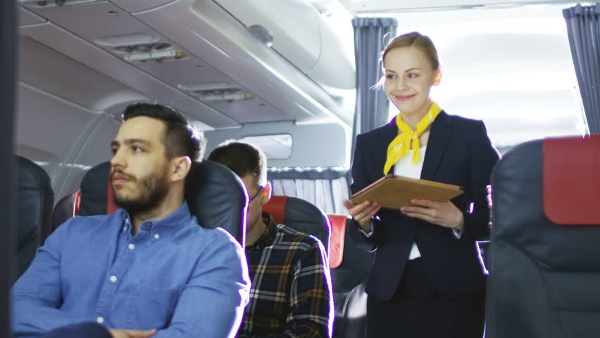 Airplane Stewardess/ Flight Attendant Shows Tablet Computer with Menu to Hispanic Male Passenger. They're Inflight. Business Class of a Commercial Aviation Interior is Visible. Shot on RED EPIC-W 8K