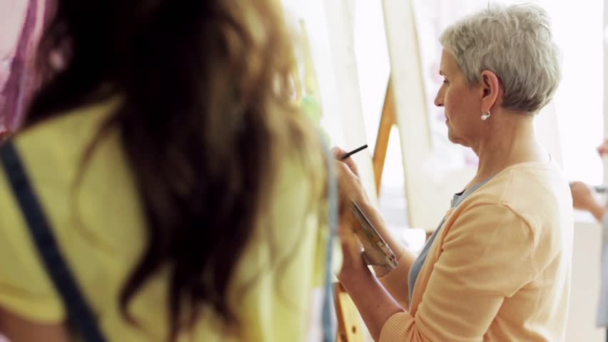art school, creativity and people concept - group of students with easels, paintbrushes and palettes painting still life at studio Royalty-Free Stock Footage #28622800
