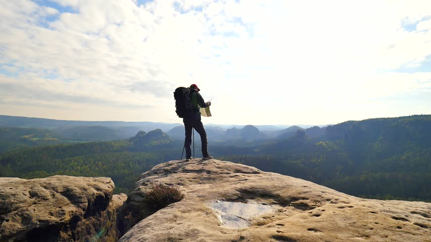 Silhouette of young tourist guide looking in paper  map in nature while hiking.  Man hiker with heavy backpack. Trekking in rocks | Shutterstock HD Video #28623571