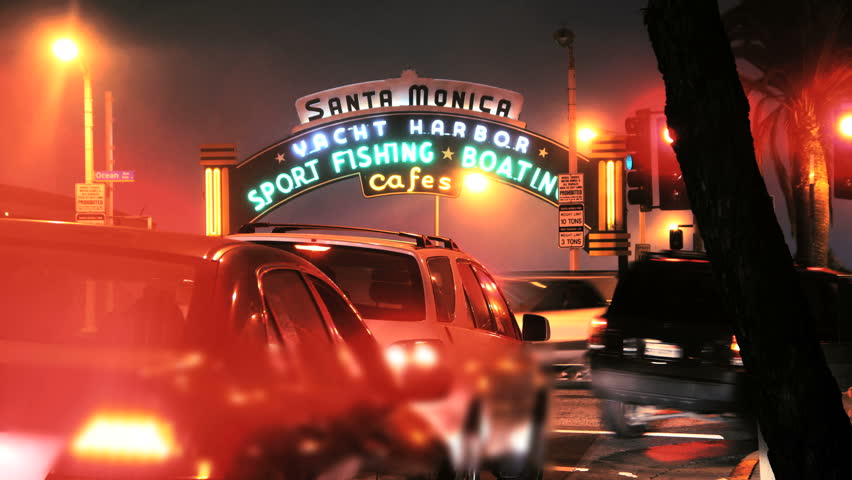 SANTA MONICA - JULY 15: Time lapse of cars and tourists passing by the iconic fishing pier in Santa Monica, California on July 15th, 2011. Zoom in to sign