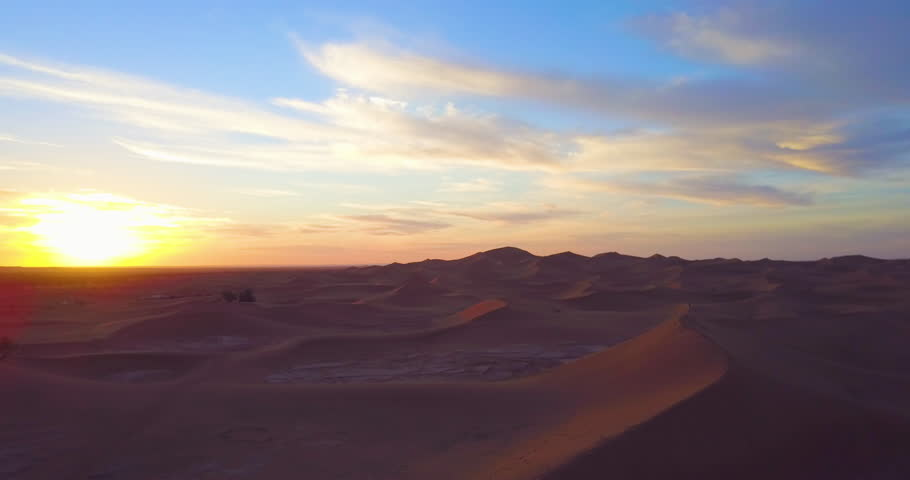Morocco-2010s: A remarkable aerial over desert sand dunes and a small village at sunrise in Morocco. | Shutterstock HD Video #28631272