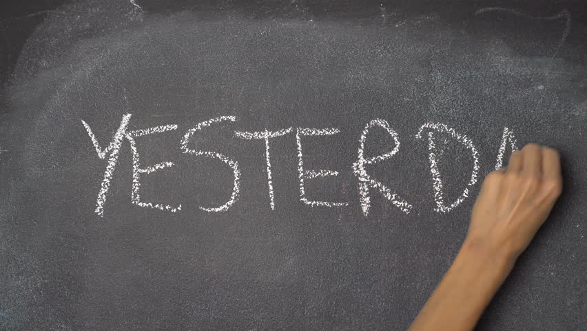 """Woman's hand writing """"TODAY, YESTERDAY, TOMORROW"""" with white chalk on blackboard"""