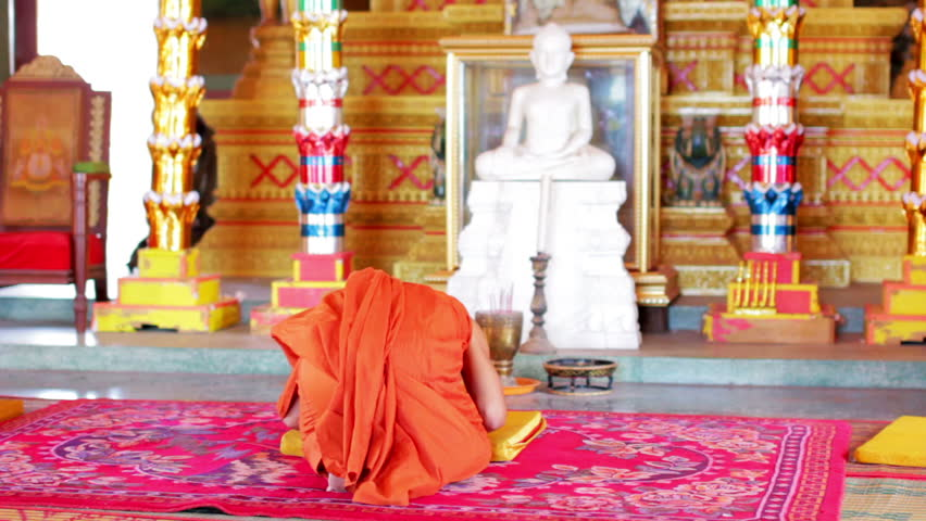 a view of a buddhist monk with orange robe pray in temple