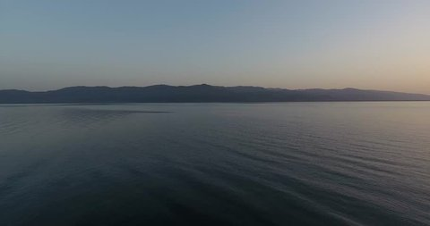 4K aerial view of lake Trichonida in Greece. Fast tracking shot of rippled water and on lake. Reflection of clouds is falling in water. Filmed from surface level perspective.
