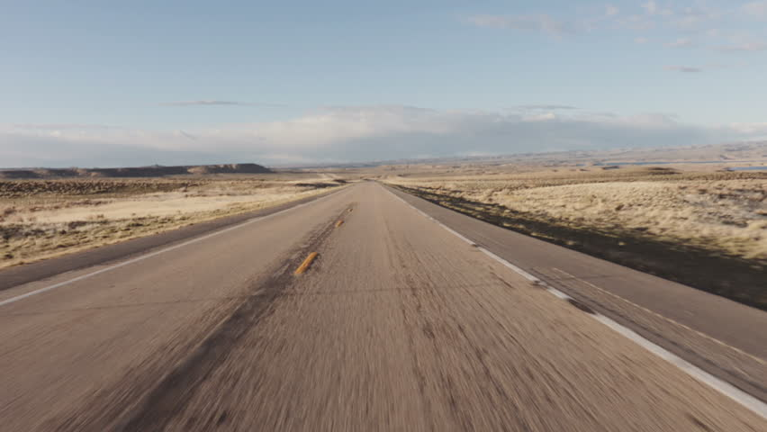 Driving USA: The open road – beautiful point of view shot driving on long straight road in desert grasslands at sunrise/sunset, Wyoming