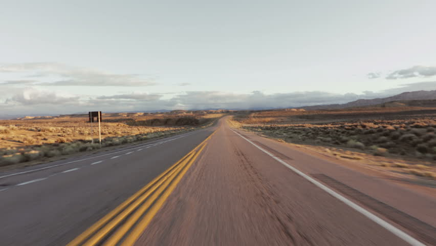 Driving USA: The open road – spectacular point of view car shot speeding across desert grasslands at sunrise or sunset, Wyoming