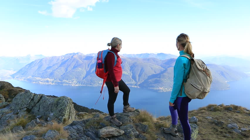 Two females friends hikers reaching mountain top celebrating with a high five hand  | Shutterstock HD Video #28663270