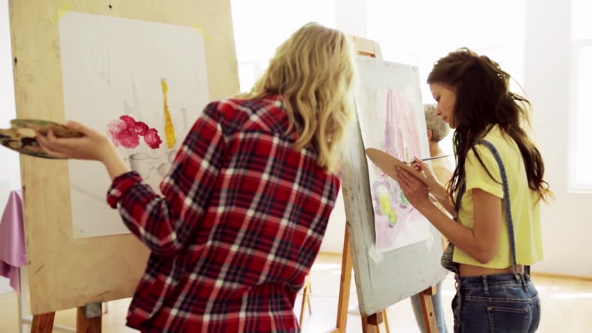 art school, creativity and people concept - group of students with easels and palettes painting still life at studio Royalty-Free Stock Footage #28670434