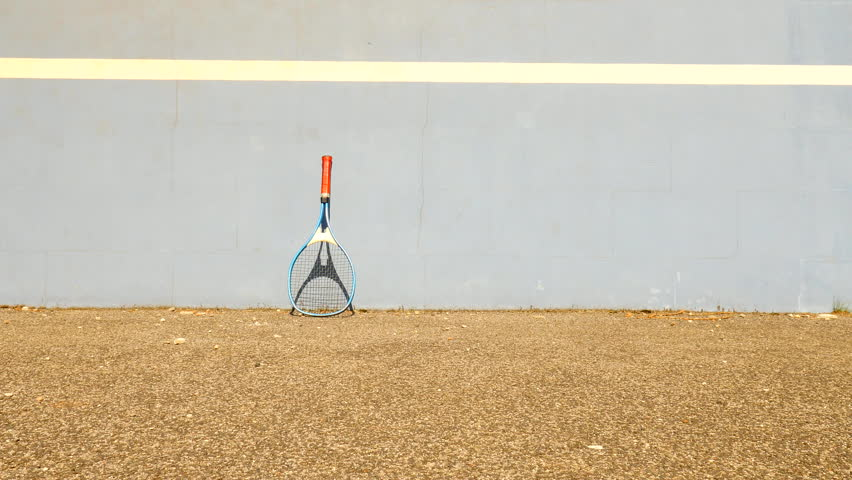 Empty training tennis court with blue bouncing tennis wall. Old yellow ball is jumping on the poor asphalt ground