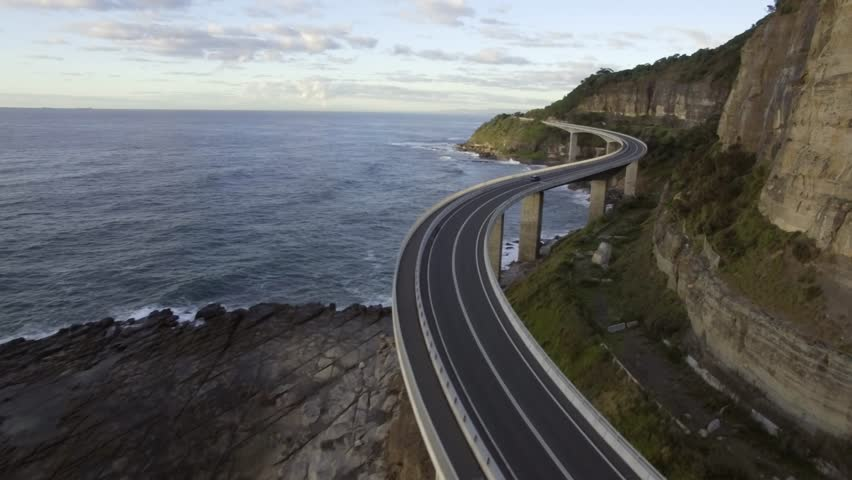 Drone flies under Sydney Sea Cliff Bridge and skims along the ocean