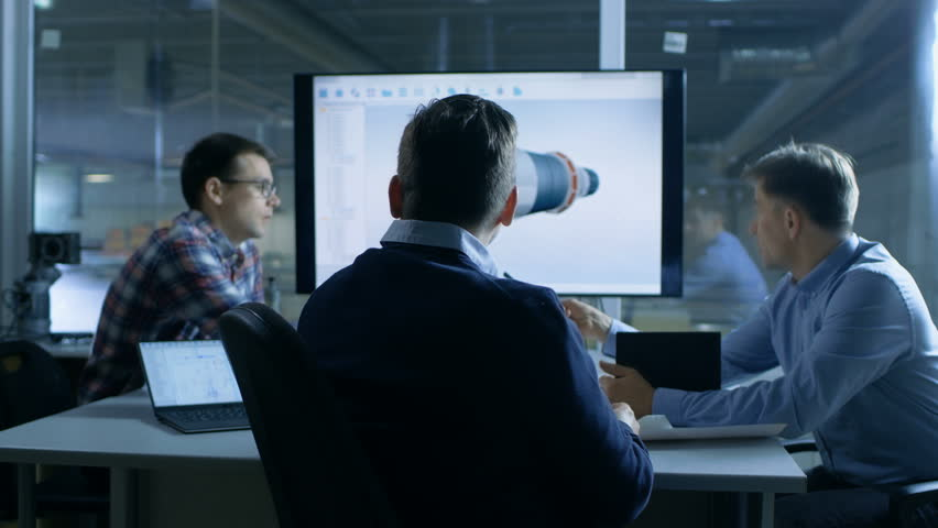 Team of Industrial Engineers Discuss 3D Turbine/ Engine Part Design Shown on a Presentation Display. In the Background Factory is Seen. Shot on RED EPIC-W 8K Helium Cinema Camera.