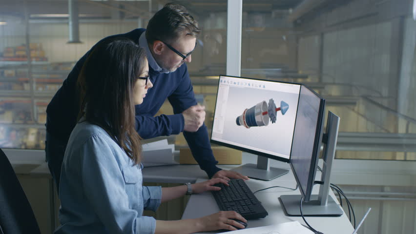 Female Industrial Engineer and Male Project Manager Work on 3D Turbine/ Engine Model in Her CAD Software. Inside of the Factory is Seen From the Office Window. Shot on RED EPIC-W 8K Helium  Camera. | Shutterstock HD Video #28699018