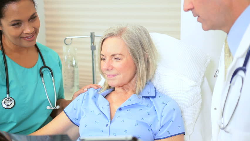 Hospital staff using wireless tablet technology discussing x-ray result with patient | Shutterstock HD Video #2870065