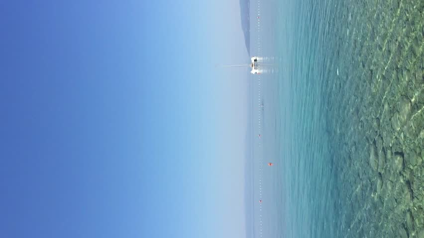 One lonely yacht drifting on waves in beautiful Adriatic Sea.Fantastic seascape under the clear blue sky.Vertical video.Crystal clear water for diving.Exotic tropical travel destination for summer Royalty-Free Stock Footage #28702954
