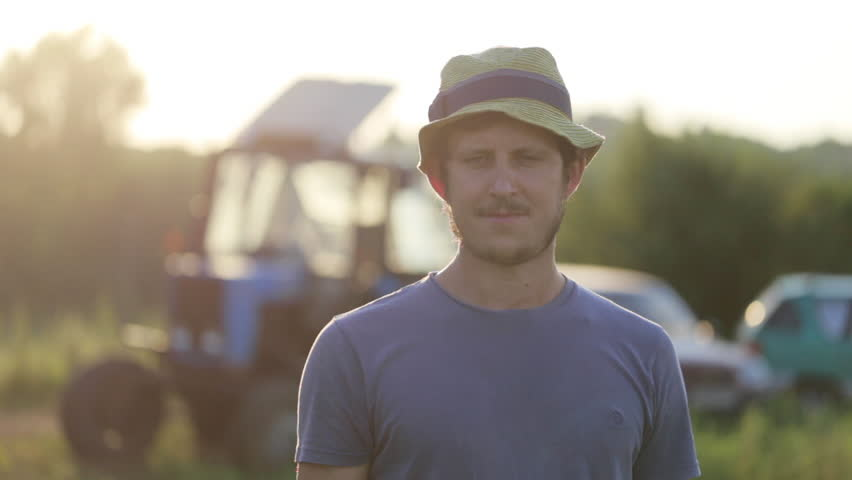 Portrait of young farmer in hat standing at field of organic farm with the tractor on the background. Man looking at camera and smiling in beautiful sunset light.