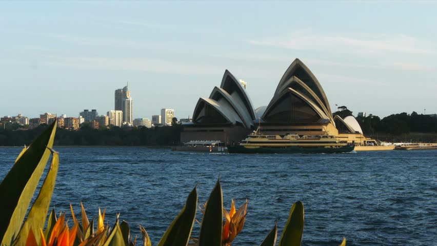 SYDNEY, AUSTRALIA - September 26: Sydney Opera House, view from Milson Pt, on September 26, 2012 with bird of paradise flowers in bloom and the Manly ferry in the foreground
