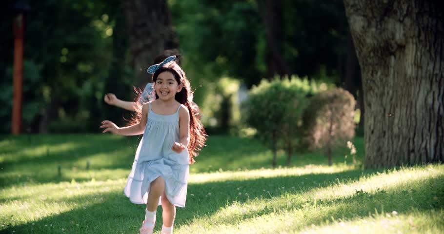 Children running around in garden and laughing,slow motion
