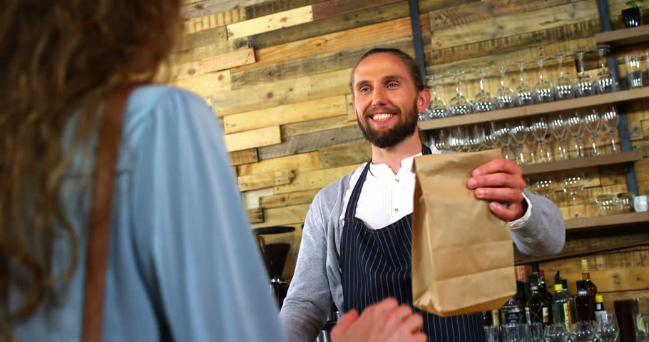 Waiter giving parcel to female costumer at counter in café   Shutterstock HD Video #28712836