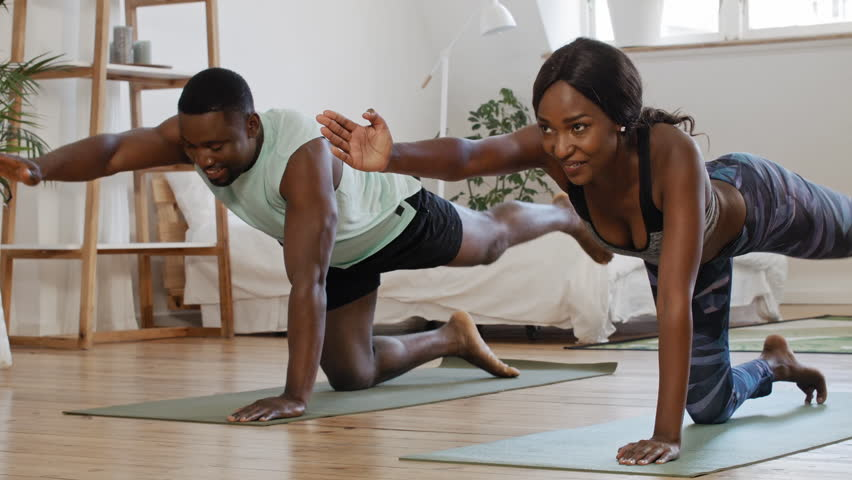 Young attractive couple practicing yoga stretching workout at home, healthy lifestyle body care