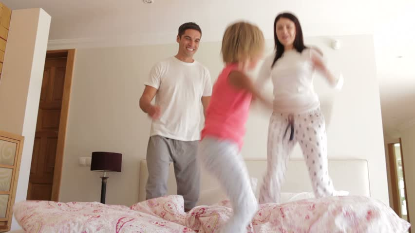 Young girl bounces excitedly on bed with parents.
