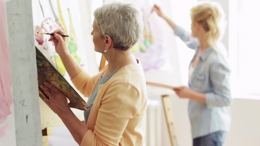 art school, creativity and people concept - group of students with easels, paintbrushes and palettes painting still life at studio Royalty-Free Stock Footage #28736542
