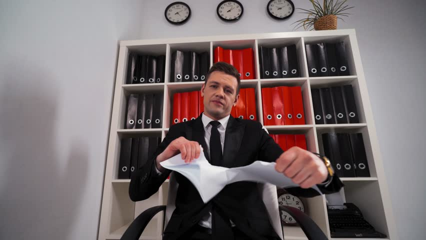 Angry handsome businessman tearing up a document, contract or agreement with You sitting in office armchair. Paper pieces. Termination docs with clients by company concept.