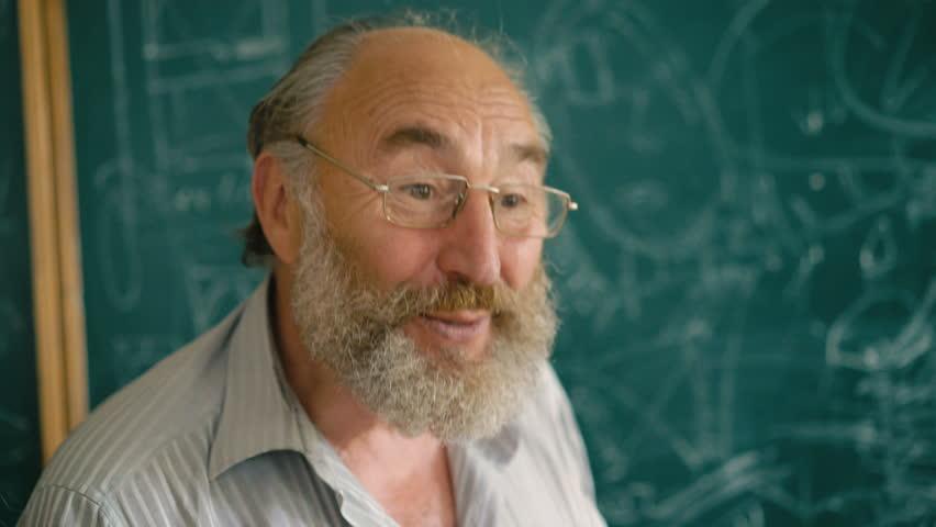 A charismatic nervous teacher explaining with facial expression near blackboard | Shutterstock HD Video #28739260