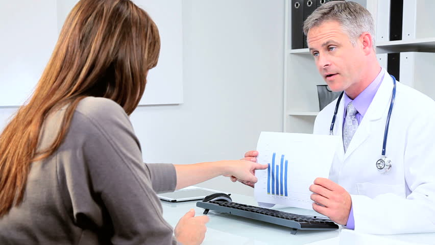 Female pharmaceutical representative meeting doctor responsible for clinical trials in his practice rooms